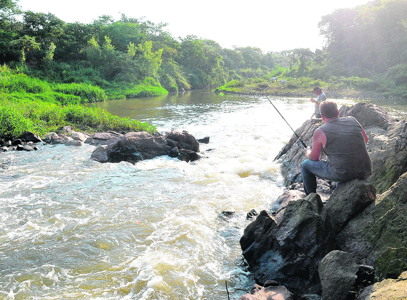 Homens pescam em trecho do Rio Camanducaia: má qualidade da água fez com que a ANA vetasse a construção de barragem em Amparo